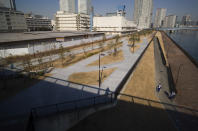 Security guards, bottom right, pass by each other as they patrol the closed area of the riverbank adjacent to a closed building complex, back left, built to be used for the athletes' village during the rescheduled Tokyo Olympics, in Tokyo on Thursday, Jan. 21, 2021. The postponed Tokyo Olympics are to open in just six months. Local organizers and the International Olympic Committee say they will go ahead on July 23. But it's still unclear how this will happen with virus cases surging in Tokyo and elsewhere around the globe. (AP Photo/Hiro Komae)