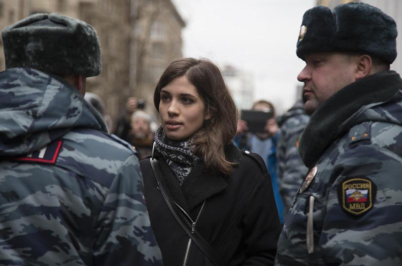 Member of the Pussy Riot punk group, Nadezhda Tolokonnikova, center, speaks to a police officer outside Zamoskvoretsky District Court in Moscow, Russia, Monday, Feb. 24, 2014, where hearings started against opposition activists detained on May 6, 2012 during the rally at Bolotnaya Square. A Moscow judge on Friday, Feb. 21, 2014, convicted eight anti-government protesters of rioting during a 2012 protest against Vladimir Putin, following a trial seen as part of the Kremlin's efforts to stifle dissent. (AP Photo/Alexander Zemlianichenko)