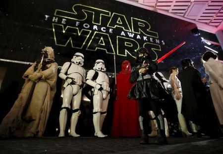 """Moviegoers wait before the first showing of the movie """"Star Wars: The Force Awakens"""" at the entrance of a movie theatre in Tokyo"""