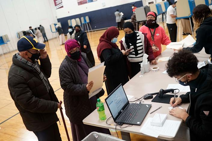 Dawleh Ahmed, left center, and Naji Ahmed, left, wait in line to vote at Salina Elementary School on Nov. 3, 2020, in Dearborn, Mich.