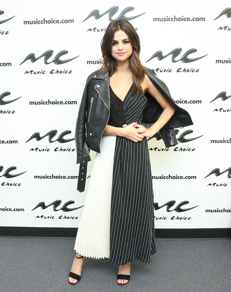 <p>Selena visited Music Choice in a monochrome panelled dress and a leather jacket, June 2017. </p>