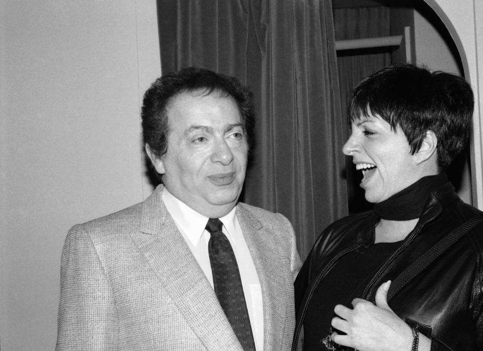 """FILE - In this Feb. 4, 1991, file photo, Liza Minnelli chats with comic Jackie Mason during a visit backstage at the Neil Simon Theater in New York. Minnelli had dropped by to congratulate Mason on his new Broadway show, """"Brand New."""" Mason, a rabbi-turned-jokester whose feisty brand of standup comedy got laughs from nightclubs in the Catskills to West Coast talk shows and Broadway stages, has died. He was 93. Mason died Saturday, July 24, 2021, in Manhattan, the celebrity lawyer Raoul Felder told The Associated Press. (AP Photo/Michael Simon, File)"""