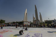 Students led pro-democracy protesters write massages in a massive white-fabric during a protest rally at the Democracy monument in Bangkok, Thailand, Saturday, Nov. 14, 2020 (AP Photo/Sakchai Lalit)