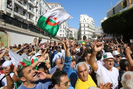 Demonstrators carry national flags and shout slogans during a protest against a proposed new hydrocarbons law in Algiers