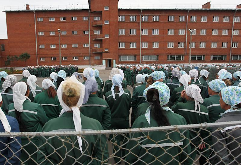 """In this photo taken Aug. 22, 2012 imprisoned women stand during a morning inspection at a women's prison in a town of Sarapul, central Russia. Two members of the punk band Pussy Riot will serve their sentence in a penal colony far from Moscow that is like what a former inmate describes as a """"nasty Girl Scout camp."""" Although Russia's prison system is a far cry from Stalin's gulag, the principle remains the same: to isolate people from their families and wear them down through """"corrective labor,"""" which for women usually means hunching over a sewing machine. Maria Alyokhina and Nadezhda Tolokonnikova will have to quickly learn the inner laws of prison life, survive the dire food and medical care, and risk reprisal from inmates either offended by their """"punk prayer"""" against President Vladimir Putin or ordered to pressure them by higher authorities. (AP Photo/Yuri Tutov)"""