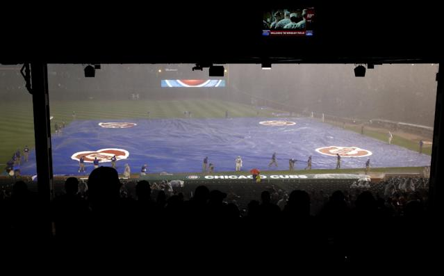 The tarp covers the field during a rain delay in the second inning of the Baltimore Orioles-Chicago Cubs interleague baseball game in Chicago, Saturday, Aug. 23, 2014. (AP Photo/Nam Y. Huh)