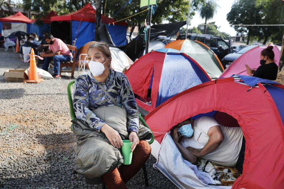 Relatives of COVID-19 patients camp outside the Ingavi Hospital in San Lorenzo, Paraguay, Wednesday, June 2, 2021. The relatives maintain a round-the-clock vigil to provide the food and medicines for their hospitalized family members. (AP Photo/Jorge Saenz)