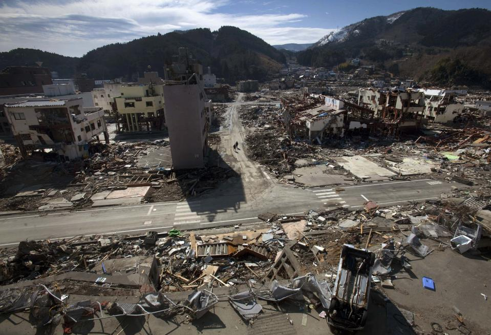 In this March 19, 2011, file photo, residents of the tsunami and earthquake destroyed town of Onagawa in Miyagi Prefecture, northern Japan, walk down an empty street. (AP Photo/David Guttenfelder, File)