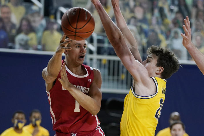 Wisconsin guard Jonathan Davis (1) passes the ball around Michigan guard Franz Wagner (21) during the first half of an NCAA college basketball game Tuesday, Jan. 12, 2021, in Ann Arbor, Mich. (AP Photo/Carlos Osorio)