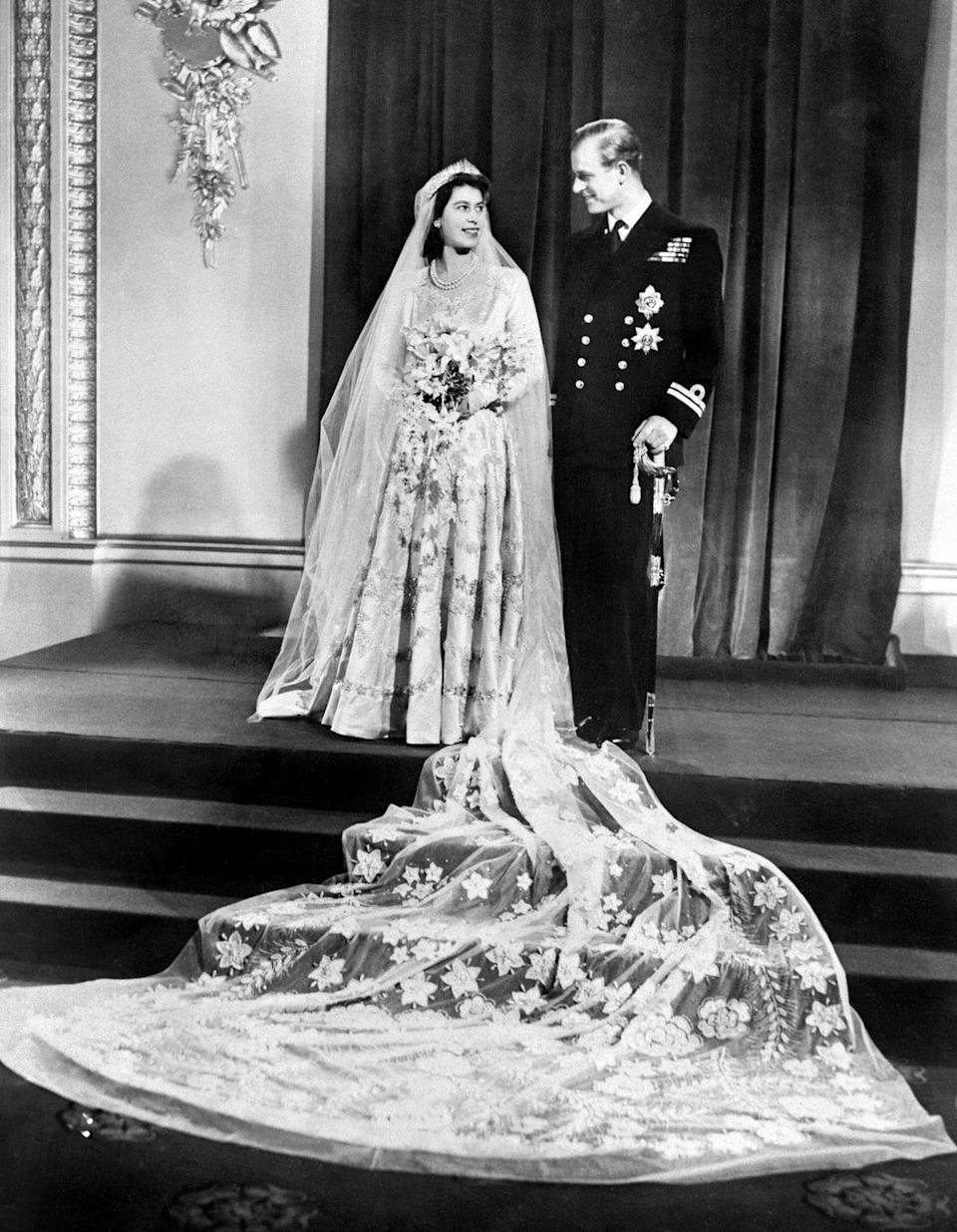 "<p>Designer Norman Hartnell had the honor of designing Her Majesty's rich duchesse satin dress, which drew inspiration from Botticelli's painting <a href=""http://www.italianrenaissance.org/a-closer-look-botticellis-primavera/"" rel=""nofollow noopener"" target=""_blank"" data-ylk=""slk:Primavera"" class=""link rapid-noclick-resp""><em>Primavera</em></a>. The dress was made of silk from China (not Japan or Italy, given the proximity to World War II) and was intended to symbolize ""<a href=""http://www.townandcountrymag.com/society/tradition/a13438510/queen-elizabeth-wedding-dress/"" rel=""nofollow noopener"" target=""_blank"" data-ylk=""slk:rebirth and growth"" class=""link rapid-noclick-resp"">rebirth and growth</a>."" The queen famously saved up ration cards to pay for the dress, which took 350 women seven weeks to create.</p>"