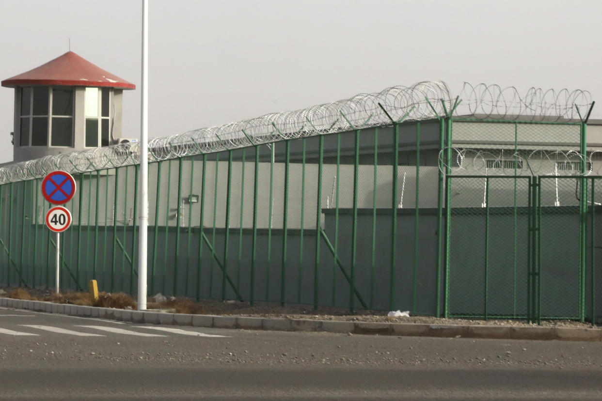 FILE - In this Monday, Dec. 3, 2018, file photo, a guard tower and barbed wire fence surround a detention facility in the Kunshan Industrial Park in Artux in western China's Xinjiang region.