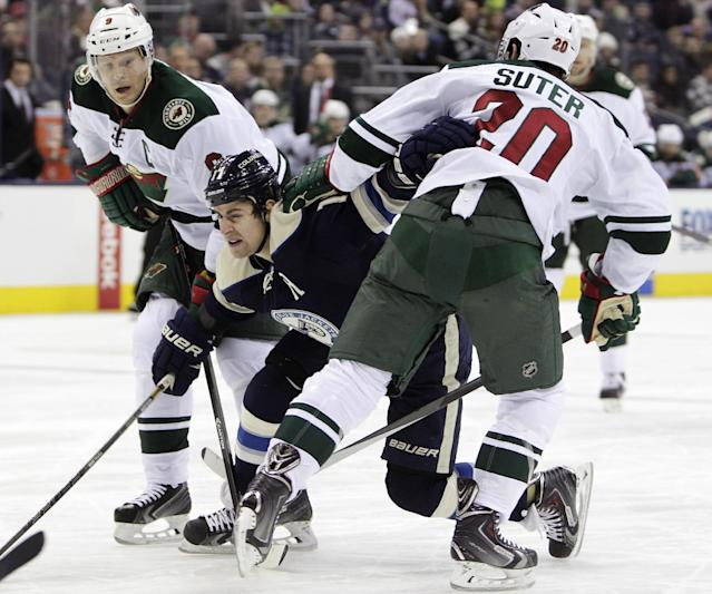 Columbus Blue Jackets' Brandon Dubinsky, center, tries to carry the puck between Minnesota Wild's Mikko Koivu, left, of Finland, and Ryan Suter during the second period of an NHL hockey game on Friday, Dec. 6, 2013, in Columbus, Ohio. (AP Photo/Jay LaPrete)