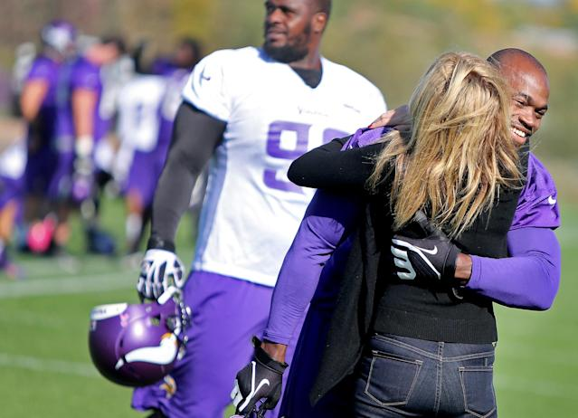 Minnesota Vikings' Adrian Peterson, right, receives a hug from an unidentified person during an NFL football practice field at Winter Park in Eden Prairie, Minn., Friday, Oct. 11, 2013. Peterson said he is certain he will play Sunday despite a serious personal matter that caused him to miss practice earlier this week. (AP Photo/The Star Tribune, Elizabeth Flores)