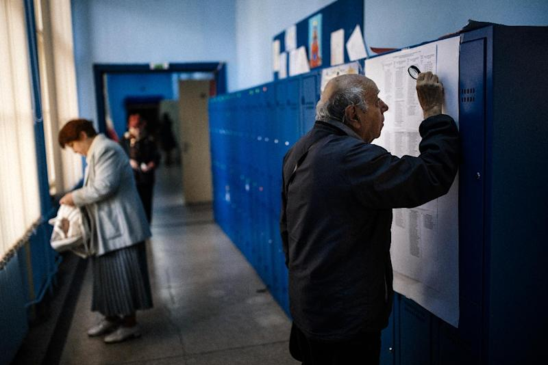 A man looks through a magnifying glass at the names of candidates in the general election at a polling station in Sofia on October 5, 2014 (AFP Photo/Dimitar Dilkoff )