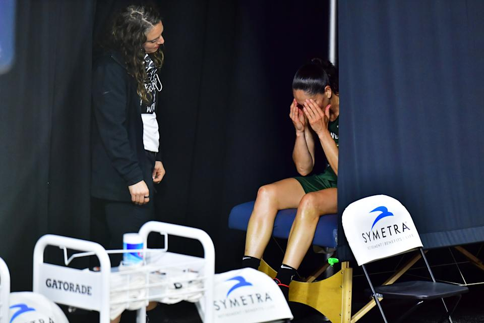 Sue Bird with a trainer on the sideline.