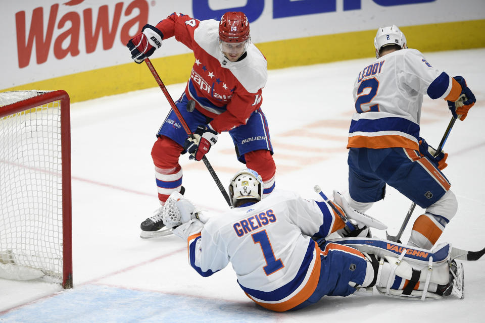 Washington Capitals right wing Richard Panik (14), New York Islanders goaltender Thomas Greiss (1) and Nick Leddy battle for the puck during the first period of an NHL hockey game, Monday, Feb. 10, 2020, in Washington. (AP Photo/Nick Wass)