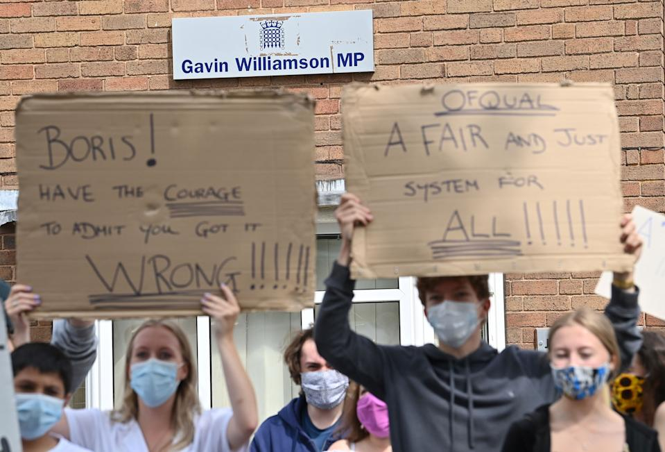 Students hold placards as they protest outside of the constituency office for Gavin Williamson, Conservative MP for South Staffordshire and Britain's current Education Secretary, in Codsall near Wolverhampton, central England on August 17, 2020, to demonstrate against the downgrading of A-level results. - The British government faced criticism after education officials downgraded more than a third of pupils' final grades in a system devised after the coronavirus pandemic led to cancelled exams. Although the newly released results for 18-year-olds showed record-high grades and more students accepted to university courses, exam boards downgraded nearly 40 percent of pupils' grades in England. (Photo by Paul ELLIS / AFP) (Photo by PAUL ELLIS/AFP via Getty Images)