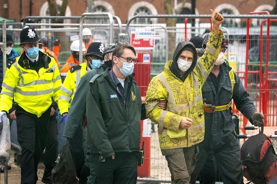 An Anti-HS2 campaigner walks with paramedics as he leaves Euston Square Gardens (Victoria Jones/PA) (PA Archive)