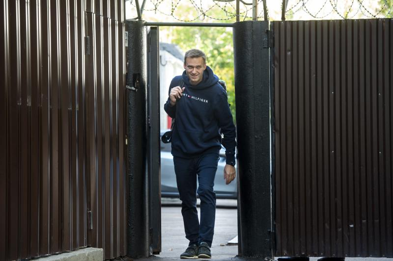 Russian opposition leader Alexei Navalny leaves a detention center after his release, in Moscow, Russia, Friday, Aug. 23, 2019. Navalny, the Kremlin's most prominent foe, was sentenced last month to 30 days for calling on people to take part in an unauthorized protest. (AP Photo/Dmitry Serebryakov)