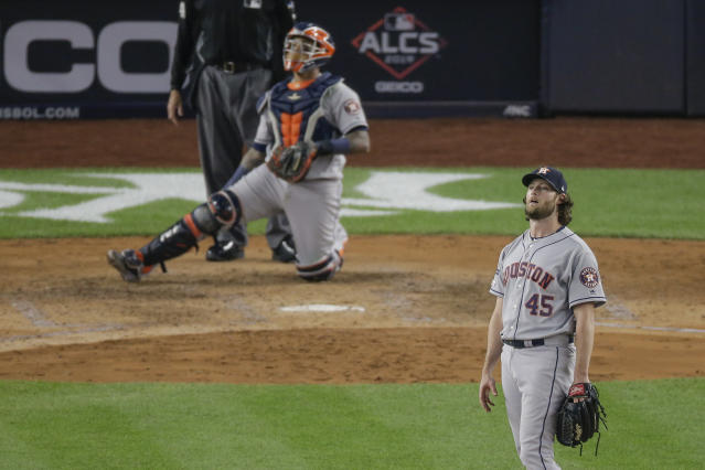Houston Astros starting pitcher Gerrit Cole (45) and catcher Martin Maldonado watch as a long drive by New York Yankees' Didi Gregorius is caught at the wall by right fielder Josh Reddick with two men on base to end the fifth inning of Game 3 of baseball's American League Championship Series, Tuesday, Oct. 15, 2019, in New York. (AP Photo/Seth Wenig)