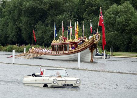 An amphibious car passes Queen Elizabeth II's royal barge Gloriana at the Thames Traditional Boat Festival near Henley-on-Thames