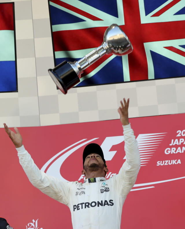 <p>Mercedes driver Lewis Hamilton of Britain throws his trophy aloft as he celebrates after winning the Japanese Formula One Grand Prix at Suzuka, Japan, Sunday, Oct. 8, 2017. (AP Photo/Eugene Hoshiko)</p>