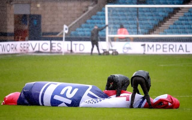 Staff struggle to hold on to a centre circle cover during high winds ahead of Millwall v West Brom (Adam Davy/PA)
