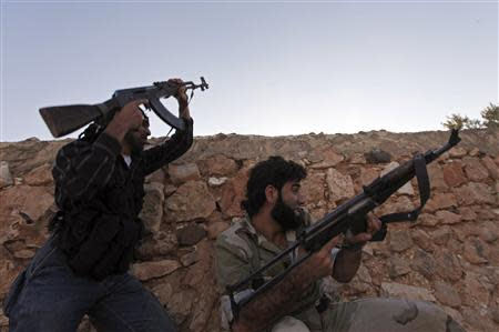 Free Syrian Army fighters fire their weapons as they take cover during clashes with what activists say are government forces, in the village of Aziza, in the southern countryside of Aleppo