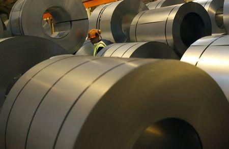 FILE PHOTO - A worker walks through coils of steel to be used on Tata Steel's new robotic welding line at their Automotive Service Centre in Wednesfield