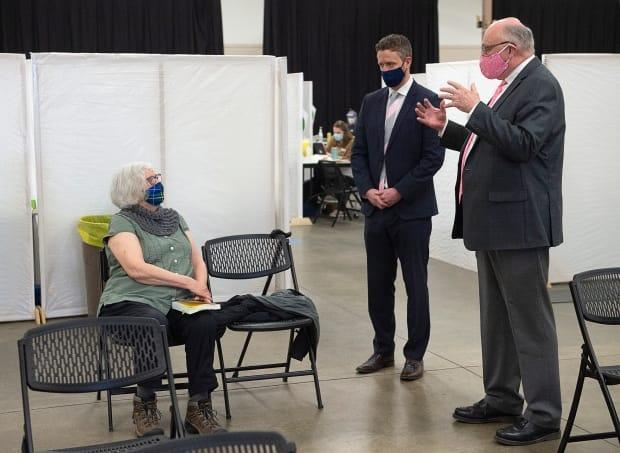 Corrie Watt, left, chats with Dr. Robert Strang, Nova Scotia's chief medical officer of health, right, and Premier Iain Rankin after receiving a COVID-19 vaccine at a clinic in Halifax on Friday, April 16, 2021.