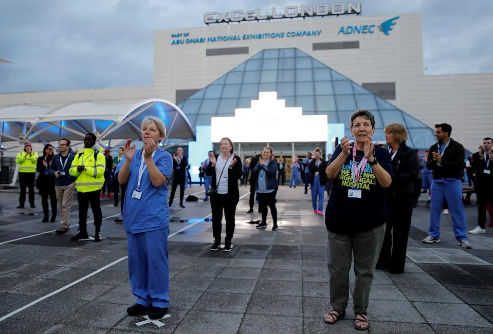 """Medical staff and workers take part in a national """"clap for carers"""" to show thanks for the work of Britain's NHS (National Health Service) workers and other frontline medical staff around the country as they battle with the novel coronavirus pandemic, outside of the ExCeL London exhibition centre, which has been transformed into the """"NHS Nightingale"""" field hospital in London on April 30, 2020. - Britain is """"past the peak"""" of its coronavirus outbreak, Prime Minister Boris Johnson said Thursday, despite recording another 674 deaths in the last 24 hours, taking the toll to 26,711. """"For the first time, we are past the peak of this disease... and we are on the downward slope,"""" Johnson said in his first media briefing since returning to work following his own fight against the virus. (Photo by Tolga AKMEN / AFP) (Photo by TOLGA AKMEN/AFP via Getty Images)"""