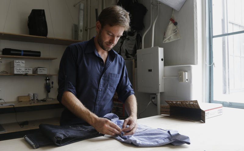 Peak Design founder Peter Dering looks through a package of clothing he had received from Buck Mason at his office in San Francisco, Monday, Sept. 30, 2013. The Silicon Valley has a fashion problem dating back to its founders, who launched high tech companies promising to be different: no more top down management, no more cubicles, no more business suits. Thus vibram shoes, hiked up jeans and stretched out t-shirts became ubiquitous in the epicenter of high tech, where brilliant innovation took place in the dumpiest of outfits. But now a younger generation of affluent, educated engineers and designers is starting to dress, and the market is responding with online men's stores that target techies, personal style consultants advising high tech executives, and an array of new men's stores at Northern California biggest mall. (AP Photo/Jeff Chiu)
