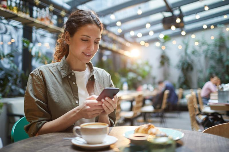 Portrait of beautiful young woman using smartphone while enjoying evening on outdoor terrace in cafe or coffee shop, copy space