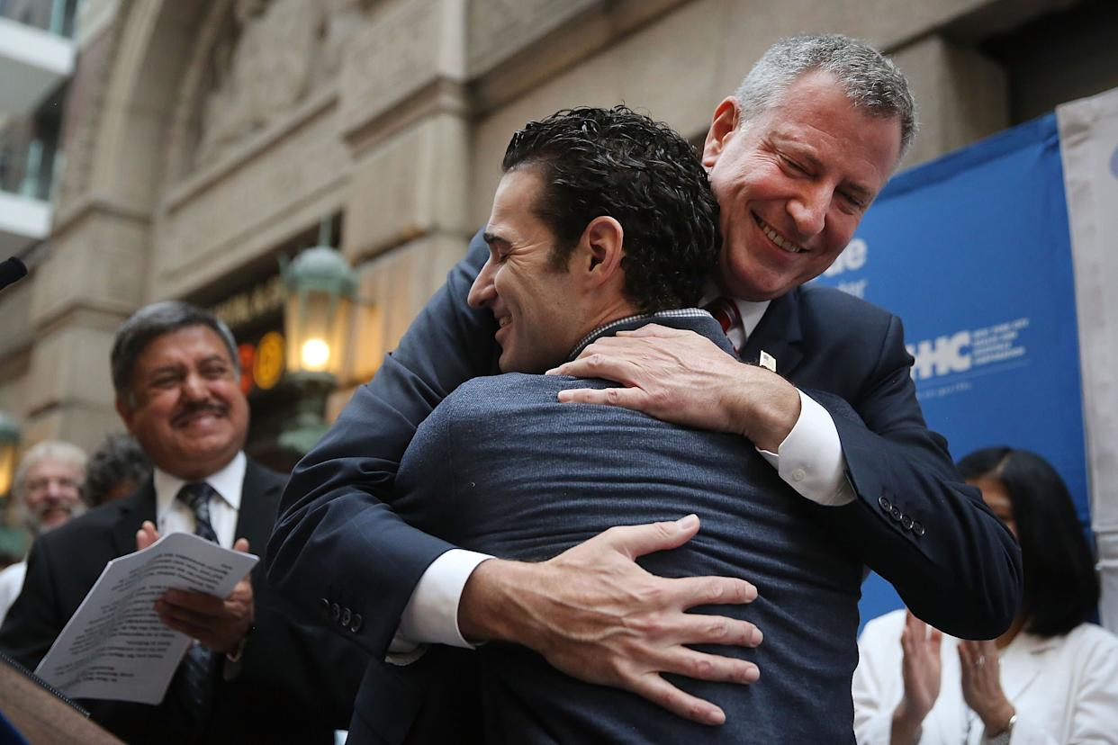 Dr. Craig Spencer, who was diagnosed with Ebola in New York City last month, hugs New York Mayor Bill de Blasio at a news conference at New York's Bellevue Hospital after being declared free of the disease on November 11, 2014.