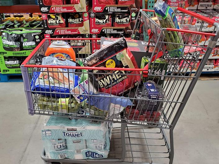 A full Costco cart with protein powder and produce