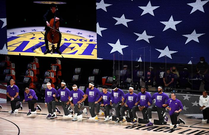 Lakers players and coaches lock arms as they listen to L.A. Philharmonic celloist Ben Hong play the national anthem.