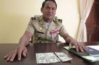 Battambang police chief Brigadier General Sar Theth poses with notes from a seized haul of $7.16 million in counterfeit hundred-dollar bills, in Battambang September 30, 2014. REUTERS/Andrew RC Marshall
