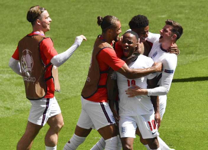 England's Raheem Sterling is congratulated by teammates after scoring his team's first goal during the Euro 2020 soccer championship group D match between England and Croatia at Wembley stadium in London, Sunday, June 13, 2021. (AP Photo/Justin Tallis, Pool)