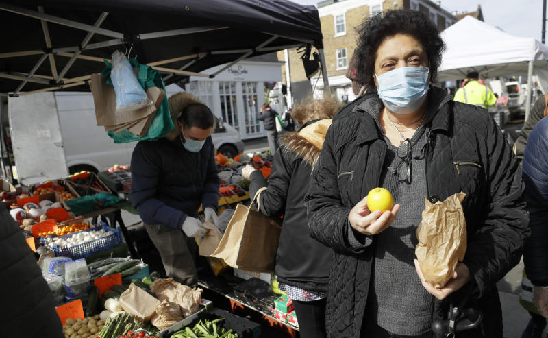 A woman wears a mask as she shops at a fruit and vegetable stall in Portobello Road market in London, Saturday, March 21, 2020. For most people, the new coronavirus causes only mild or moderate symptoms, such as fever and cough. For some, especially older adults and people with existing health problems, it can cause more severe illness, including pneumonia.(AP Photo/Kirsty Wigglesworth)