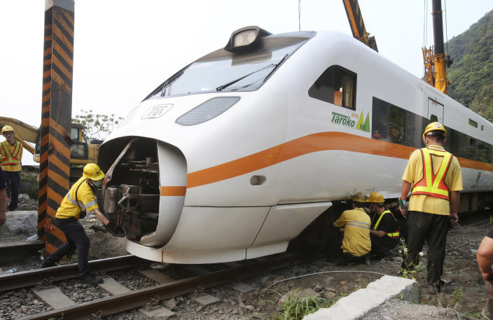 Rescue workers remove a part of the derailed train near Taroko Gorge in Hualien, Taiwan on Saturday, April 3, 2021. The train partially derailed in eastern Taiwan on Friday after colliding with an unmanned vehicle that had rolled down a hill, killing and injuring dozens. (AP Photo/Chiang Ying-ying)