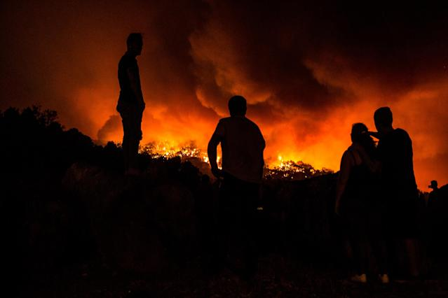 <p>People stand next to the fire before being evacuated at the village of Monchique, in southern Portugal's Algarve region, Sunday, Aug. 5 2018. (Photo: Javier Fergo/AP) </p>