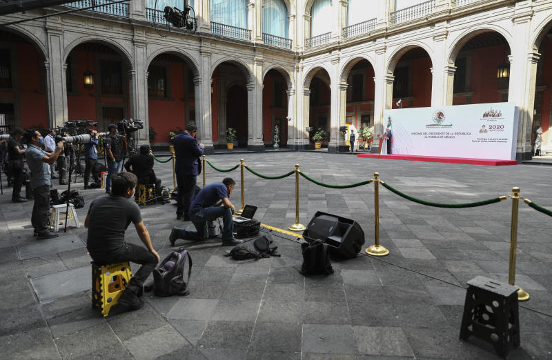 "Mexican President Andres Manuel Lopez Obrador speaks at the National Palace in Mexico City, as the press keeps their distance, Sunday, April 5, 2020. Mexico's Treasury reduced its forecast for the year this week to a contraction of the Mexican economy, which was already in a technical recession. Mexico's government has broadened its shutdown of ""non essential activities,"" and prohibited gatherings of more than 50 people as a way to help slow down the spread of COVID-19. (AP Photo/Eduardo Verdugo)"