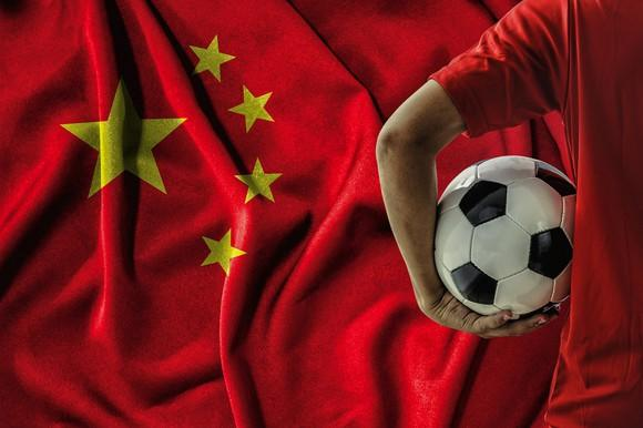 A man holds a soccer ball in front of a Chinese flag.