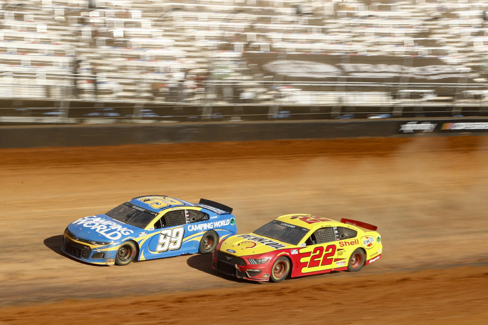 Driver Joey Logano (22) races with Daniel Suarez (99) through Turn 4 during a NASCAR Cup Series auto race, Monday, March 29, 2021, in Bristol, Tenn. (AP Photo/Wade Payne)