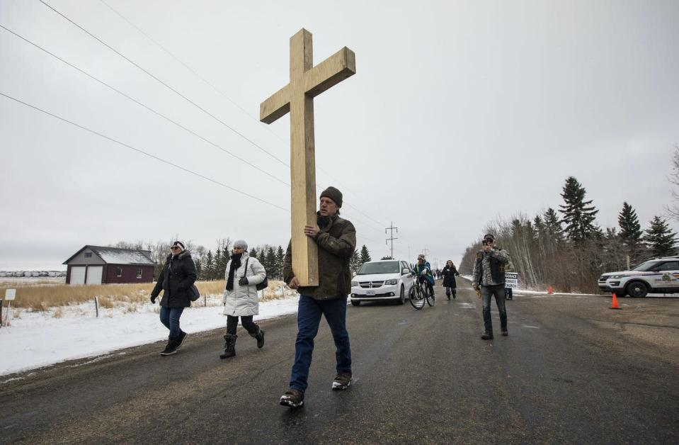 A man walks down a road carrying a large wooden cross.