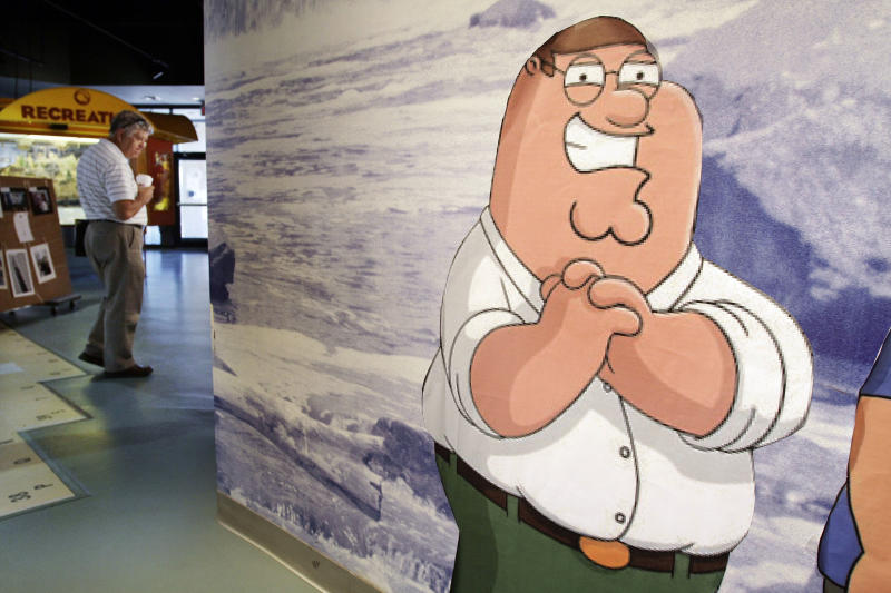 "In this Sept. 23, 2010 photo, a likeness of cartoon character Peter Griffin, from the Fox animated program the ""Family Guy"" stands in the Rhode Island Visitor's Center, in Pawtucket, R.I.  Fans of the show, based in the fictional Rhode Island town of Quahog, can hit the road on a bus tour highlighting a dozen sites in the state that have served as inspiration. (AP Photo/Steven Senne)"