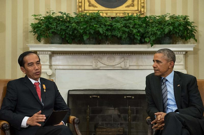 US President Barack Obama (R) listens to his Indonesian counterpart Joko Widodo speak to the press following talks in the Oval Office at the White House in Washington, DC, on October 26, 2015 (AFP Photo/Nicholas Kamm)