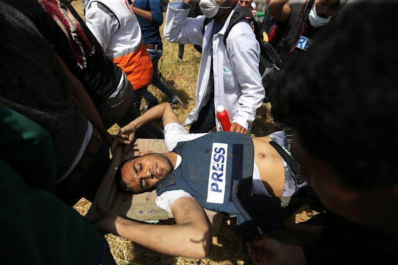 Mortally wounded Palestinian journalist Yasser Murtaja is evacuated during clashes at the Israel-Gaza border on April 6, 2018. (Ibraheem Abu Mustafa / Reuters)