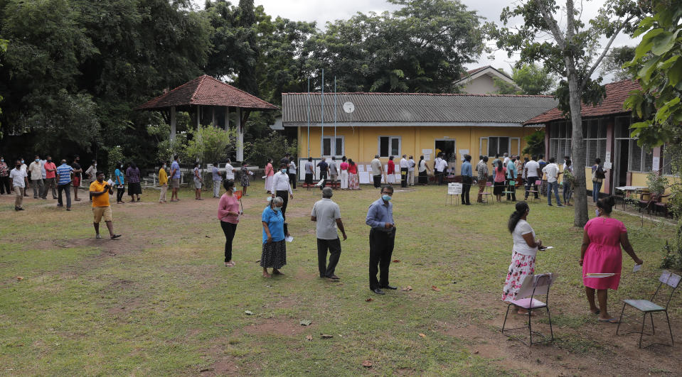 Sri Lankans stand in a queue to cast their votes outside a polling station in Colombo, Sri Lanka, Wednesday, Aug. 5, 2020. Sri Lankans started voting Wednesday to elect a new Parliament that is expected to give strong support to the powerful and popular Rajapaksa brothers. (AP Photo/Eranga Jayawardena)