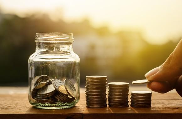 A hand putting money from rising coin stacks into a glass jar.